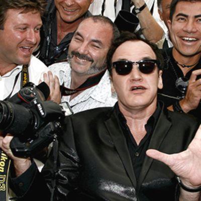 Quentin Tarantinto ilmeilee hymyilevän valokuvaajajoukon keskellä