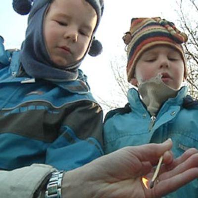Kuvassa kolme päiväkoti-ikäistä poikaa katselee sytytettyä tulitikkua.