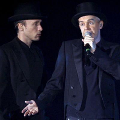 Kaksi miestä frakeissa. Vasemmalla oleva katsoo totisesti oikealla laulavaa henkilöä.
