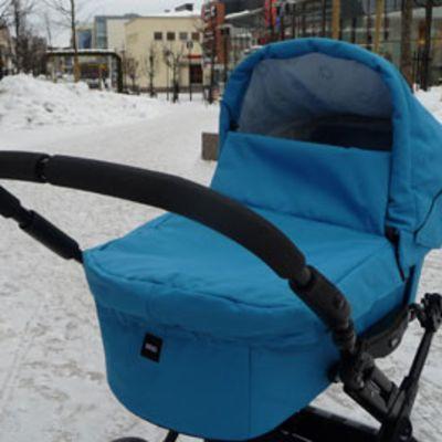 Siniset lastenvaunut lumisella kadulla.