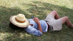 Man som ligger på gräset med en hatt över ansiktet.