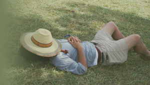 En man vilar sig på gräsmattan.