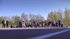 ett barn i lågstadieålder springer stafett på en idrottsplan medan funktionärer och andra deltagare ser på