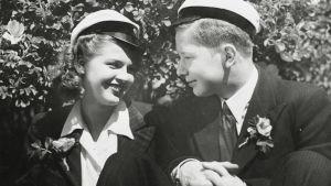 Olli (Lasse Pöysti) ja Laura (Sirkka Osmala) hymyilevät valkolakit päässään elokuvassa Suomisen Olli yllättää