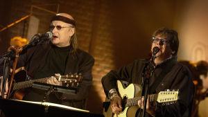 Juice Leskinen ja Mikko Alatalo esiintyvät Senaattori ja boheemi -kiertueella vuonna 2004.