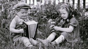 Två barn sitter i gräset. Ena spelar dragspel och andra har blommor i handen. Bilden är svartvit och från en svunnen tid.