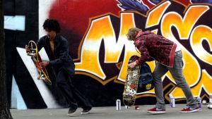 Kaksi nuorta skeittaria graffitiseinän lähellä