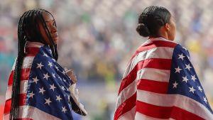 Två amerikanska idrottare har USA:s flaggor runt sig på löpbanorna.