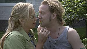 Anu Sinisalon näyttelemä nainen ja Jarkko Sarjasen näyttelemä mies ovat kuvassa kasvokkain. Nainen sivelee miehen kasvoja kukalla.