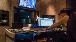 En person sitter vid mixerbordet i ett kontrollrum.