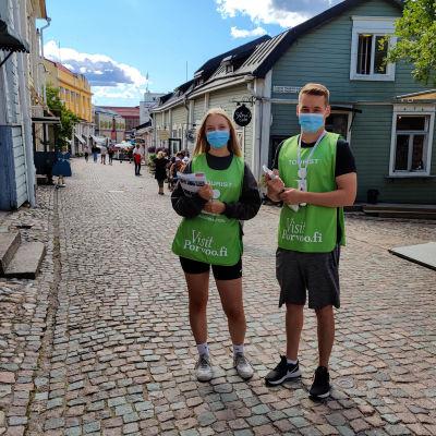 En kille och en tjej iklädda gröna västar står på en mellangatan i en stad.