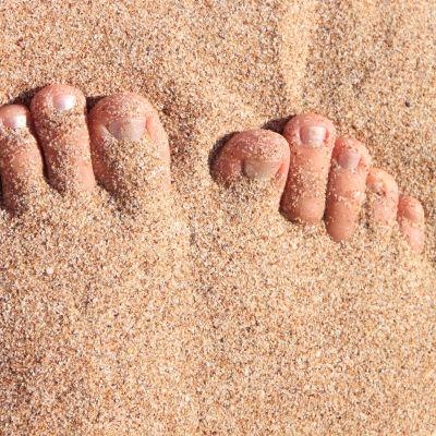 Fötter på sandstrand.