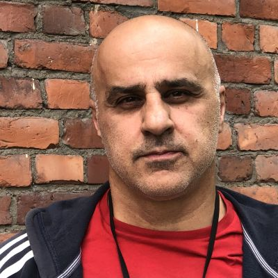 Fereidun Ahkami, som tidigare jobbat som tolk i Afghanistan, står utanför sin arbetsplats i Helsingfors.