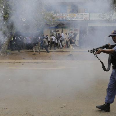 Polis avfyrar gummikulor mot invandrare under sammandrabbningar i samband med invandringsfientliga demonstgrationer i Pretoria 24.2.2017
