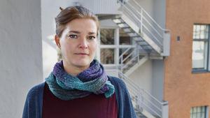 Jenni Reuter står på en balkong med handen på balkongräcket.