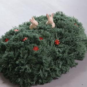 Påskgräs gjort av garn dekorerat med blommor och två keramikkaniner