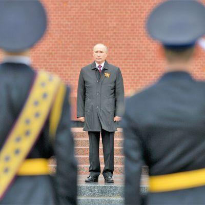 Sotilaat tekevät kunniaa Putinile, joka seisoo harmaassa päällystakissa portailla. Takana näkyy Kremlin punainen muuri.