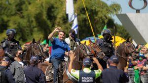 Brasiliens president Jair Bolsonaro till häst med anhängare i Brasilia 31.5.2020.