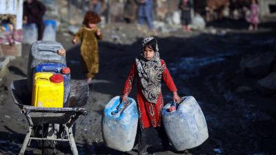 En afghansk flicka i ett flyktingläger i huvudstaden Kabul hämtar vatten från en tankbil.