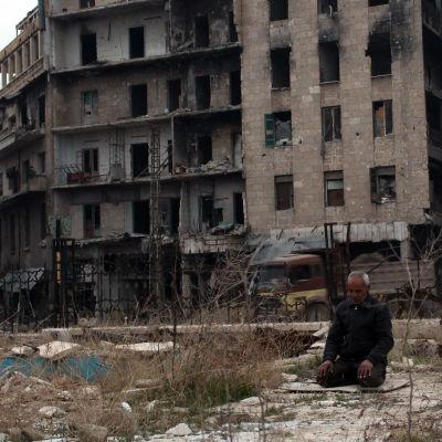 En man sitter på knä och ber i östra Aleppo, som är belägrat av rebeller. I bakgrunden övergivna byggnader skadade av striderna i staden.