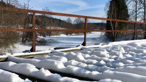 Sliten gammal snöbeklädd järnvägsbro i trä över ett vattendrag en vinterdag.