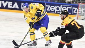 Oscar Möller slår iväg en passning framför näsan på Nikolai Goc.