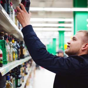 En man sträcker sig efter en flaska i en affärshylla.