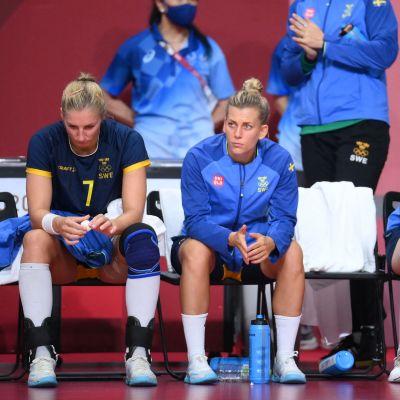 Tre svenska spelare sitter på en bänk och deppar.