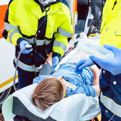 Ambulanspersonal hjälper skadad pojke