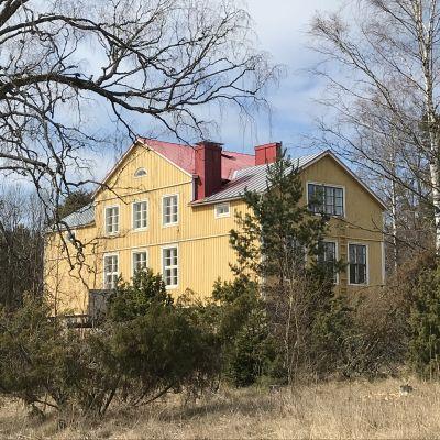 Käldinge före detta skola, en stor gul byggnad i vårgrönska.
