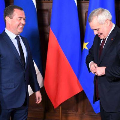 Dmitrij Medvedev och Antti Rinne, bägge klädda i mörk kostym, står framför ett antal flaggor.