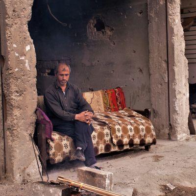 Man sitter på en soffa i första våningen av ett sönderbombat hus