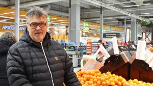 En medelålders man står i en matbutik bredvid en hög med mandariner. Han tittar in i kameran.