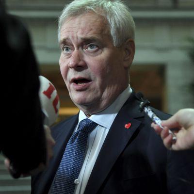 Antti Rinne med mikrofoner framför sig.