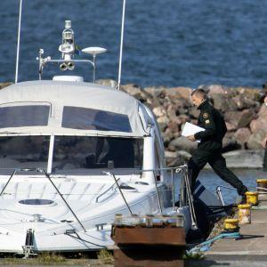Olycksutredare stiger ombord motorbåt.