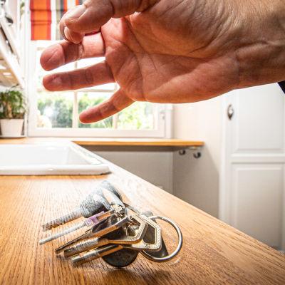 Käsi pudottaa asunnon avaimet keittiötasolle.
