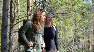 Marina och Lina går i en grön skog med ryggväskor.