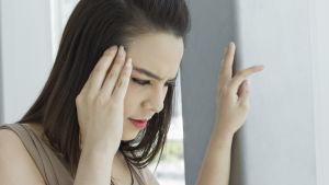 Ung kvinna håller handen vid tinningen. Stöder sig med andra handen.