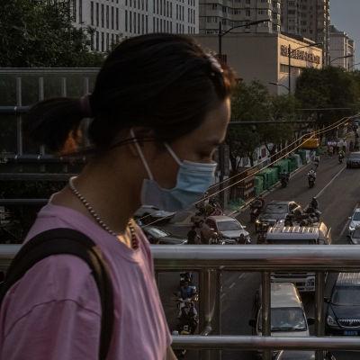 Kvinna går över bro. Bilar i trafik.
