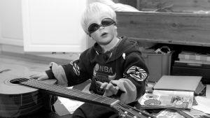 Poika soittaa kitaraa aurinkolasit päässä