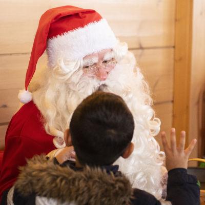 Ett barn berättar sina julklappsönskemål till julgubben.