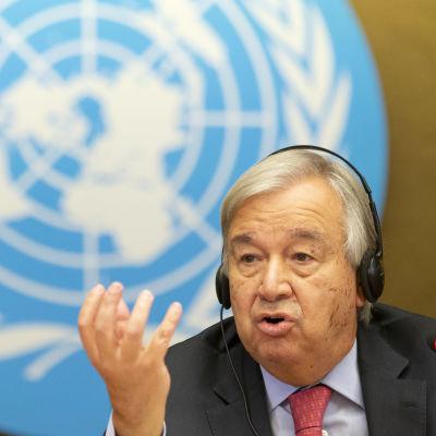 Antonio Guterres med handen i vädret, i bakgrunden FN-logon.