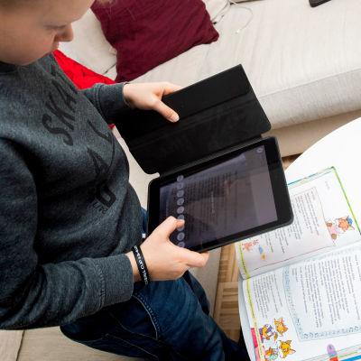 Kakkosluokkalainen poika opiskelee kotona etänä.
