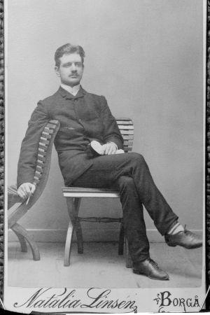 Nuori Jean Sibelius valokuvaajalla ylioppilaslakki sylissään.