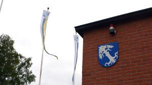 En husvägg med en vapensköld i blått synns mot en grå himmel. Bredvid vajar några vimplar med samma vapen, ett vitt träd mot blå botten.
