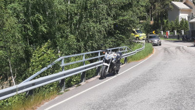 En motorcykel står vid sidan av Skärgårdsvägen, en ambulans i bakgrunden.