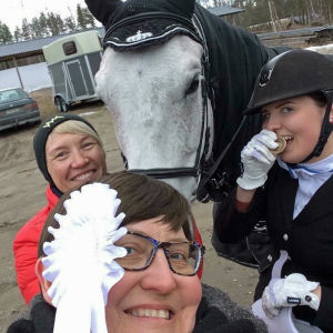 Kolme iloista naista, joista yksi ratsastusasussa mitallia hampainen välissä purren, toinen punatakkinen mustapipoinen ja kolmas etualalla valkoinen ruusuke ohimollaan sekä harmaa hapsinen hevonen