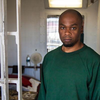 En intagen klädd i grön skjorta står vid gallret till sin cell i Atticafängelset i USA.