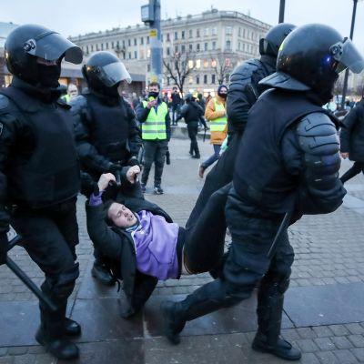 Neljä mellakkavarusteisiin pukeutunutta poliisia kantaa keskellään nuorta miestä. Taustalla näkyy aukiota.