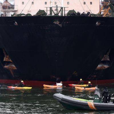Kolfartyget alppila omges av Greenpeace kajaker och båtar.